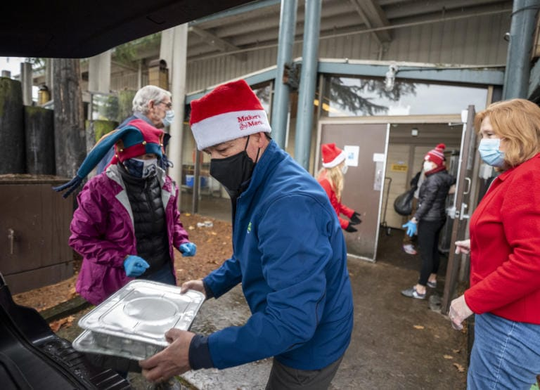 Doug Carr, center, of Battle Ground, and others load a vehicle that will deliver Christmas meals to a location in Vancouver on Friday at a Christmas meal distribution event at WareHouse '23.