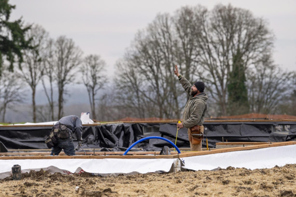A worker signals to another as they finish the foundation for Lot 21 of the Felida Overlook, a Ginn Group housing development. Vancouver is on track to issue about 65 percent more single-family home construction permits in 2020 than in the prior year, a surge fueled by a white-hot real estate market.