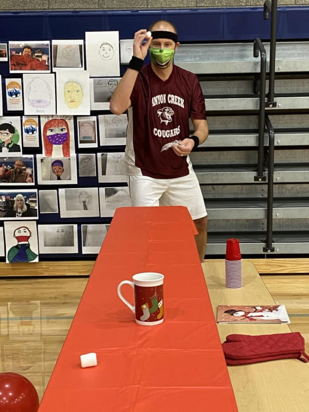 """WASHOUGAL: Canyon Creek Middle School Principal Brian Amundson takes aim in the marshmallow toss challenge. Amundson and David Cooke, from Jemtegaard Middle School, battled against each other in a series of holiday-themed """"Minute to Win It""""-style competitions on Dec."""