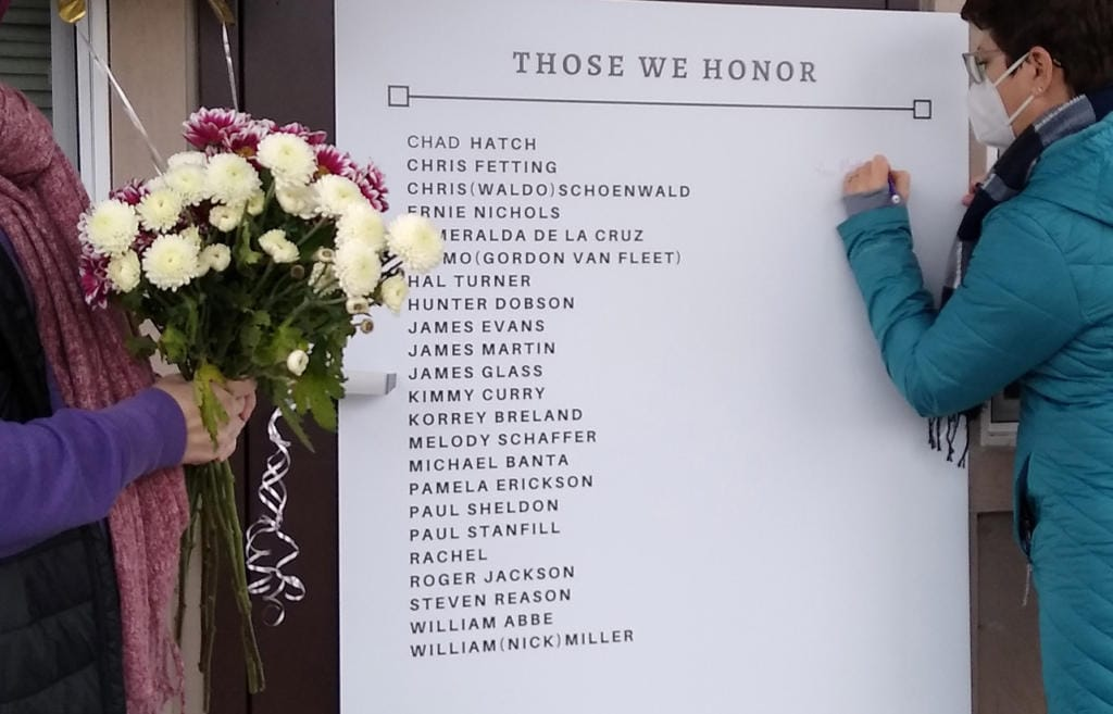 Laura Ellsworth, right, writes a message on a memorial board set up Friday at St. PaulÌs Lutheran Church in Vancouver. Ellsworth is with the Council for the Homeless, which helped set up the board with the names of the homeless from the community who died in 2020. On Monday night, the council held a virtual ceremony to remember the members of the community who died in 2020.