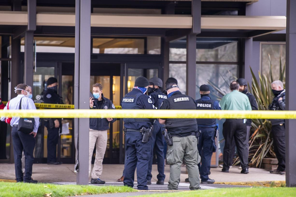 Police officers and officials congregate outside the building where a shooting reportedly happened on Tuesday, December 22, at the 505 building at the PeaceHealth Southwest Medical Center.