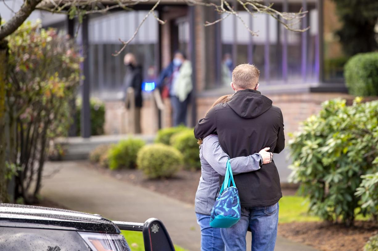 Two people embrace outside of the building where a shooting reportedly happened on Tuesday, December 22, at the 505 building at the PeaceHealth Southwest Medical Center.