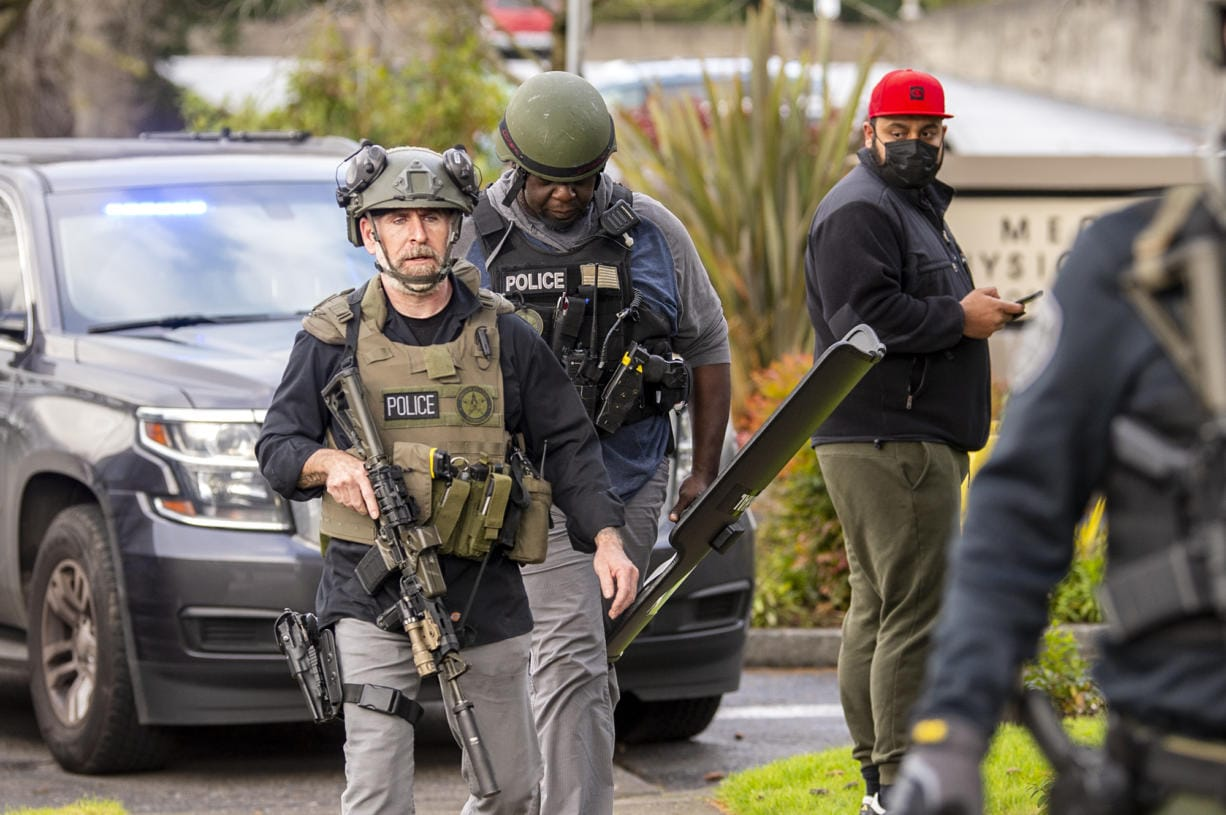 Police officers armed with assault rifles and riot shields exit the building where a shooting reportedly happened on Tuesday, December 22, at the 505 building at the PeaceHealth Southwest Medical Center.