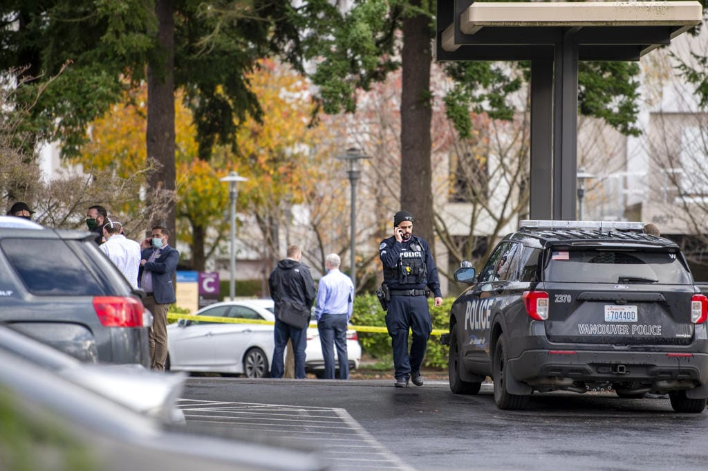 A police officer talks on his cell phone while officials congregate in front of a building where a shooting reportedly occurred on Tuesday, December 22, at the 505 building at the PeaceHealth Southwest Medical Center.