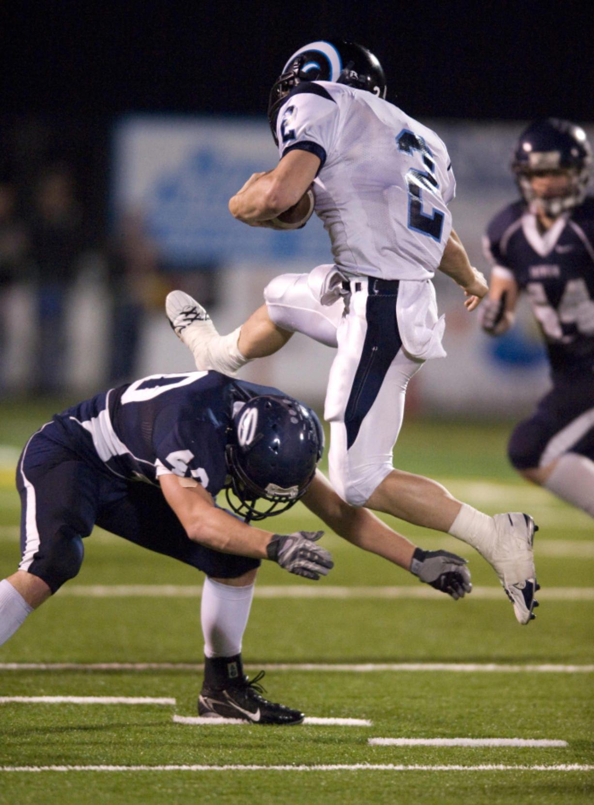 Rogers Rams QB Tyler Van Sligtenhorst, #2, leaps over Skyview LB Jason Leineweber, #40, at Kiggins Bowl, Saturday, November 15, 2008.