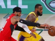 Los Angeles Lakers' LeBron James, right, drives the ball against Portland Trail Blazers'Carmelo Anthony, left.