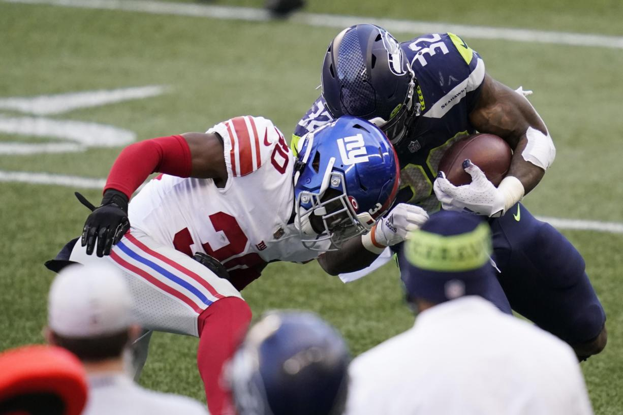 Seattle Seahawks running back Chris Carson (32) is stopped by New York Giants cornerback Darnay Holmes (30) during the second half of an NFL football game, Sunday, Dec. 6, 2020, in Seattle.