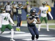 Seattle Seahawks wide receiver David Moore cradles the ball after catching a touchdown pass as New York Jets safety Matthias Farley (41) reacts behind during the second half of an NFL football game, Sunday, Dec. 13, 2020, in Seattle.