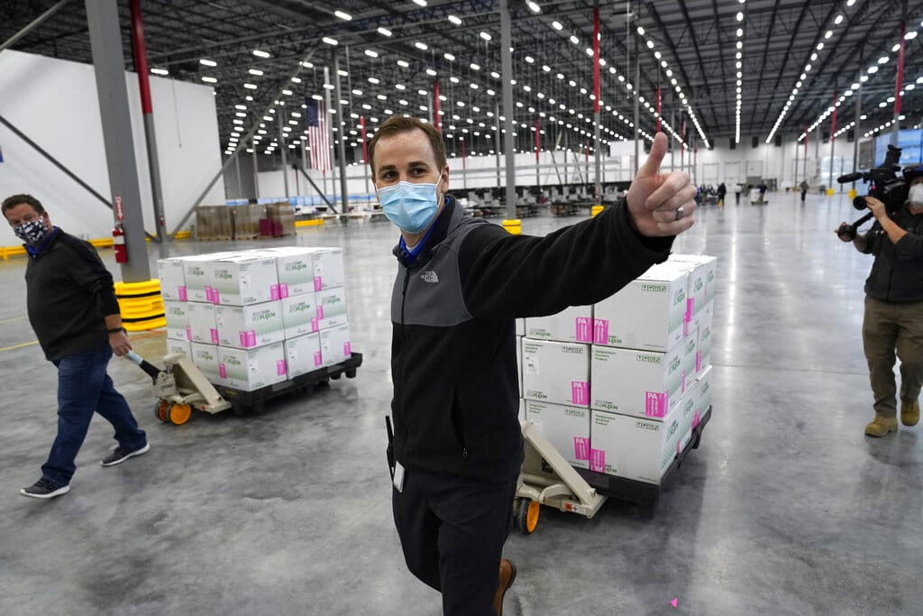 A worker gives a thumbs up while transporting boxes containing the Moderna COVID-19 vaccine to the loading dock for shipping at the McKesson distribution center in Olive Branch, Miss., Sunday, Dec. 20, 2020.