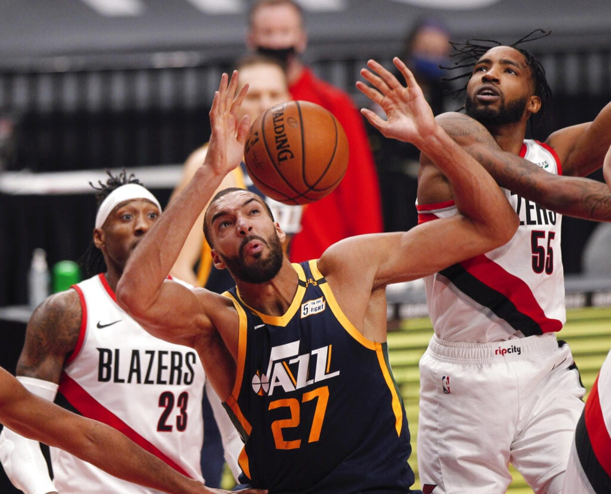 Portland Trail Blazers forward Derrick Jones Jr., right, and Utah Jazz center Rudy Gobert, middle, vie for a rebound as Trail Blazers forward Robert Covington, left, watches during the first half of an NBA basketball game in Portland, Ore., Wednesday, Dec. 23, 2020.