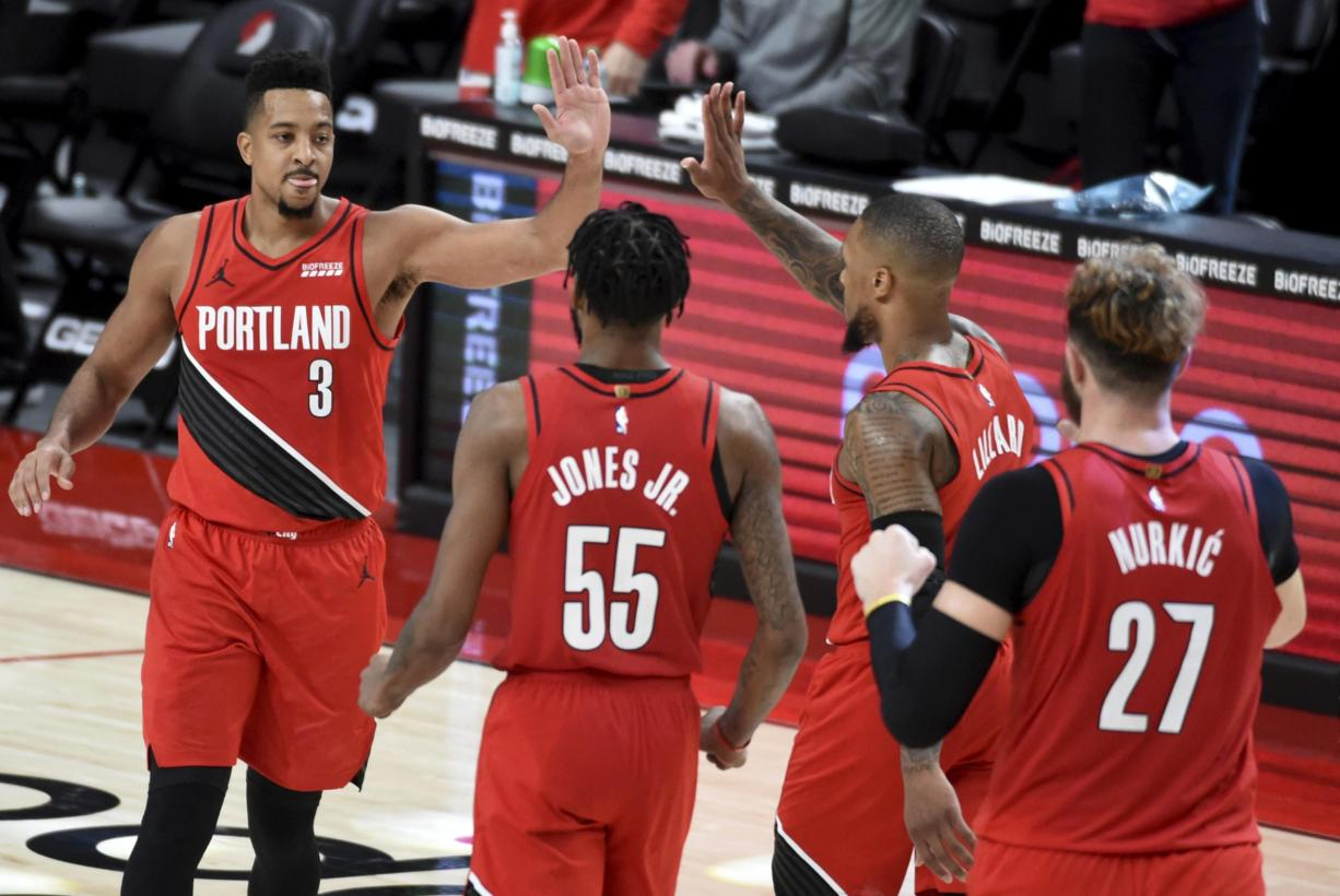 Portland Trail Blazers guard CJ McCollum, left, celebrates with teammates after hitting a shot to give the Blazers the lead late in overtime of an NBA basketball game against the Houston Rockets in Portland, Ore., Saturday, Dec. 26, 2020. The Blazers won 128-126.