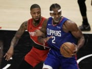 Portland Trail Blazers' Damian Lillard, left, grabs the arm of Los Angeles Clippers' Kawhi Leonard during the first half of an NBA basketball game Wednesday, Dec. 30, 2020, in Los Angeles. (AP Photo/Jae C.