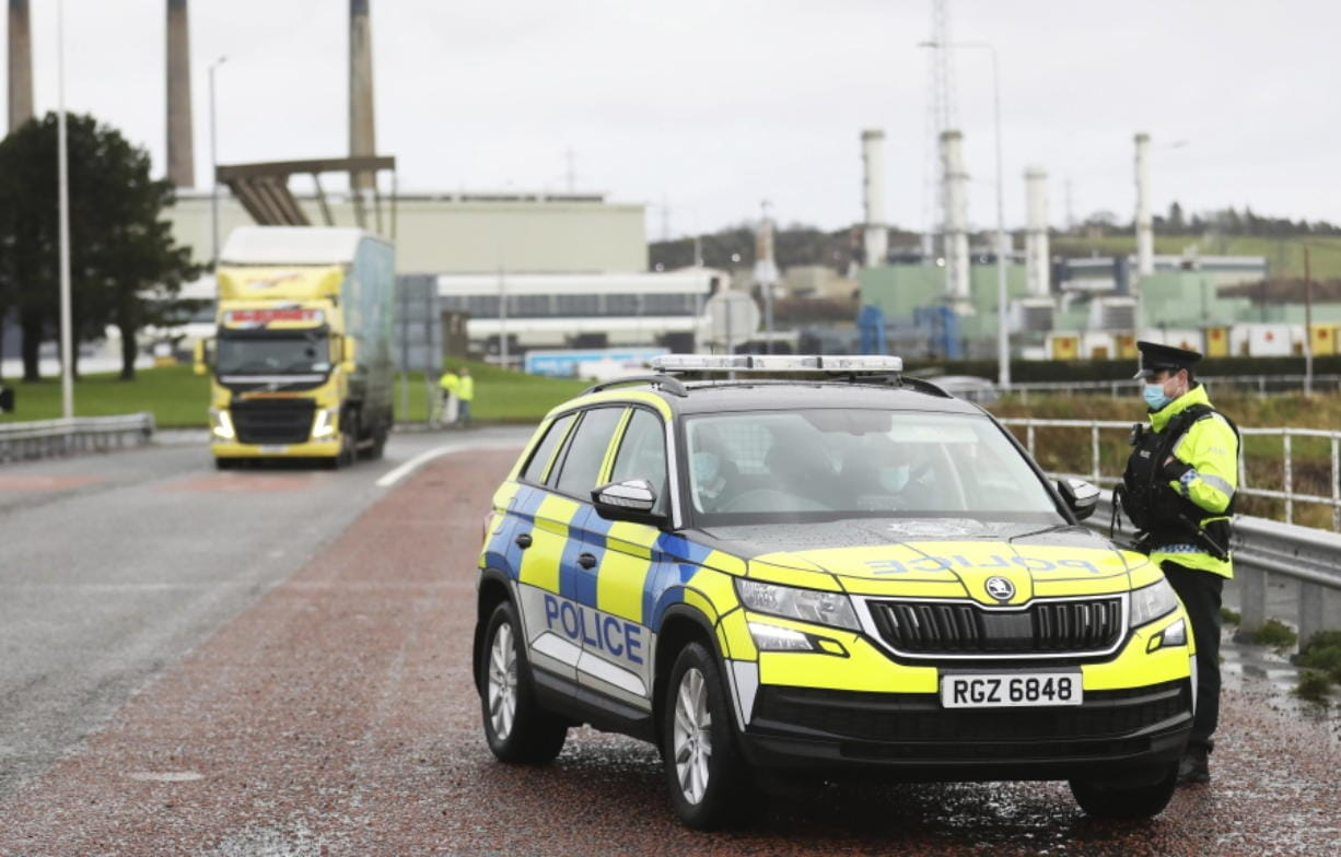 Police patrol the port of Larne, on the north coast of Northern Ireland, Thursday, Dec. 31, 2020, as the P&O ferry to Scotland prepares to leave. At 11 p.m. London time -- midnight in Brussels -- Britain will economically and practically leave the the 27-nation bloc, 11 months after its formal political departure.