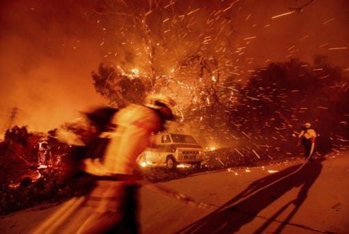 Firefighters battling the Bond Fire haul hose while working to save a home in the Silverado community in Orange County, Calif., on Thursday, Dec. 3, 2020.