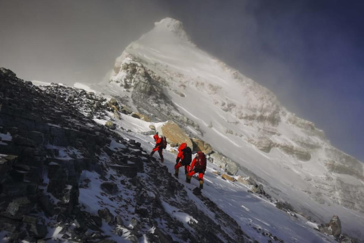 FILE - In this May 27, 2020, file photo released by Xinhua News Agency, members of a Chinese surveying team head for the summit of Mount Everest, also known locally as Mt. Qomolangma. China and Nepal have jointly announced on Tuesday, Dec. 8, 2020, a new height for Mount Everest, ending a discrepancy between the two nations.