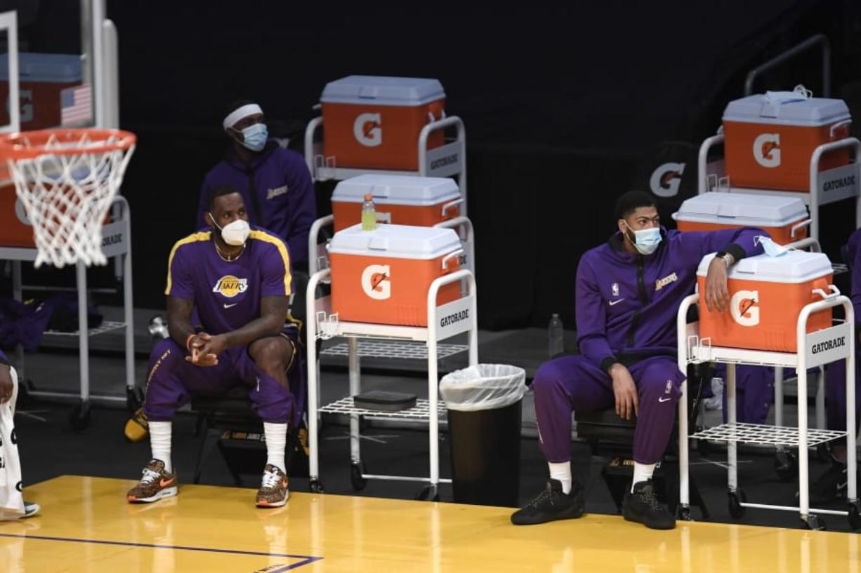 Los Angeles Lakers forward LeBron James, left, and forward Anthony Davis wear masks watch their teammates play during the first half of an NBA preseason basketball game against the Los Angeles Clippers in Los Angeles, Friday, Dec. 11, 2020. (AP Photo/Kyusung Gong) (Kevin C.
