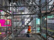 A construction worker walks down a staircase in the scaffolding of TSX Broadway under construction, Thursday, Oct. 29, 2020, in New York's, Times Square. The 46-story mixed-use property will house 75,000 square feet of retail space, a 4,000-square-foot performance venue including an outdoor stage, an outdoor food and beverage terrace and a luxury hotel. U.S. construction spending rose 0.3% in September, the fourth straight monthly gain after a coronavirus-caused spring swoon.