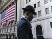 FILE - In this Nov. 16, 2020 file photo a man wearing a mask passes the New York Stock Exchange in New York. Stocks are opening moderately lower on Wall Street, edging below the record highs they set a day earlier. The S&P 500 fell 0.4% shortly after the opening bell Wednesday, Dec. 2.