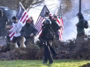 Supporters of President Donald Trump and antifa supporters clashed with Washington state police on the state Capitol Campus in Olympia, Wash., Saturday, Dec. 12, 2020. Police in Olympia declared a riot early Saturday afternoon and arrested at least one person as groups with different points of view held simultaneous protests.