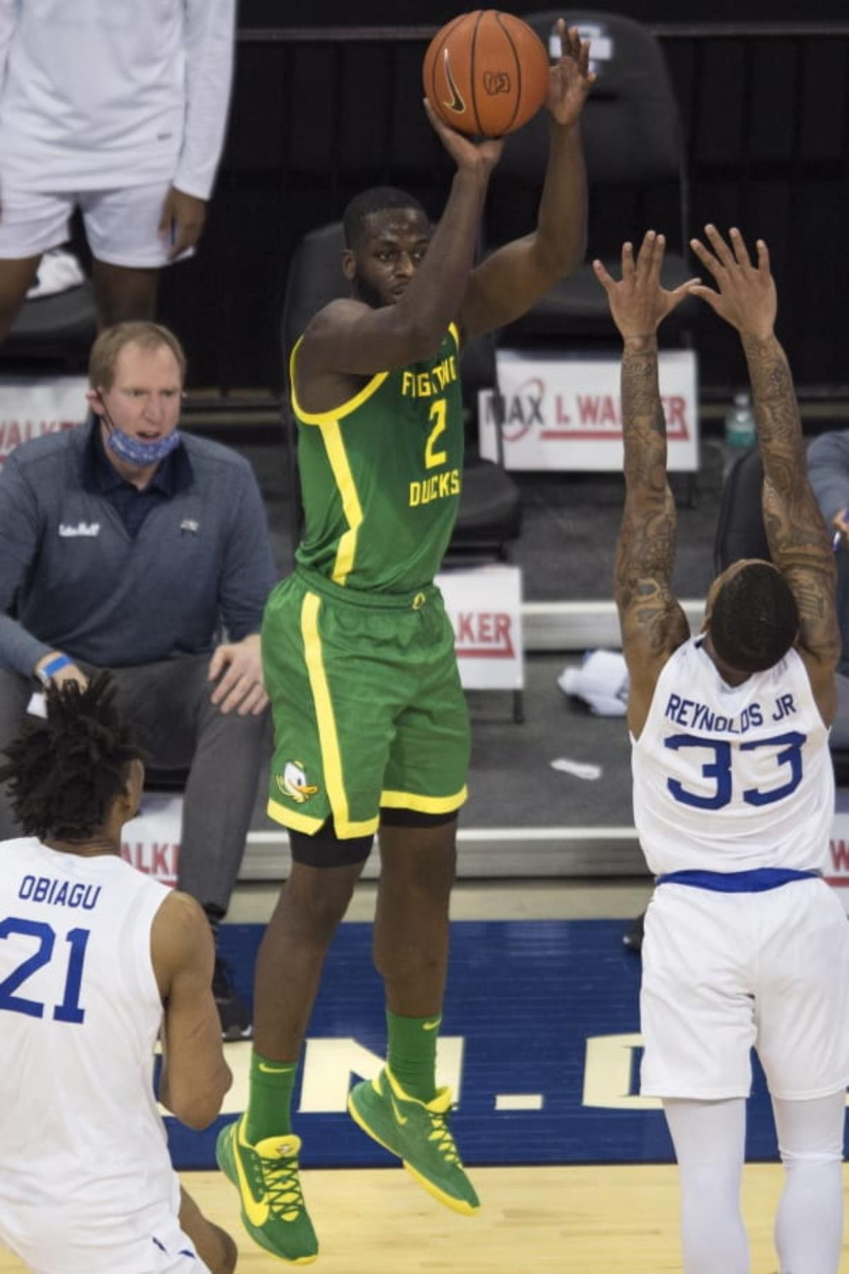 Oregon's Eugene Omoruyi scores against Seton Hall's Ike Obiagu, left, and Shavar Reynolds Jr. during the first half of an NCAA college basketball game in Omaha, Neb., Friday, Dec. 4, 2020.