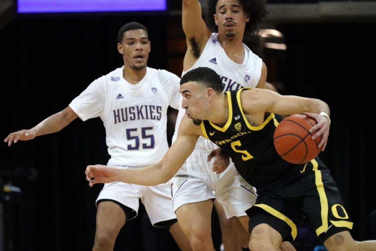 Oregon's Chris Duarte (5) tries to get past Washington's Quade Green (55) and Nate Pryor during the first half of an NCAA college basketball game Saturday, Dec. 12, 2020, in Seattle.