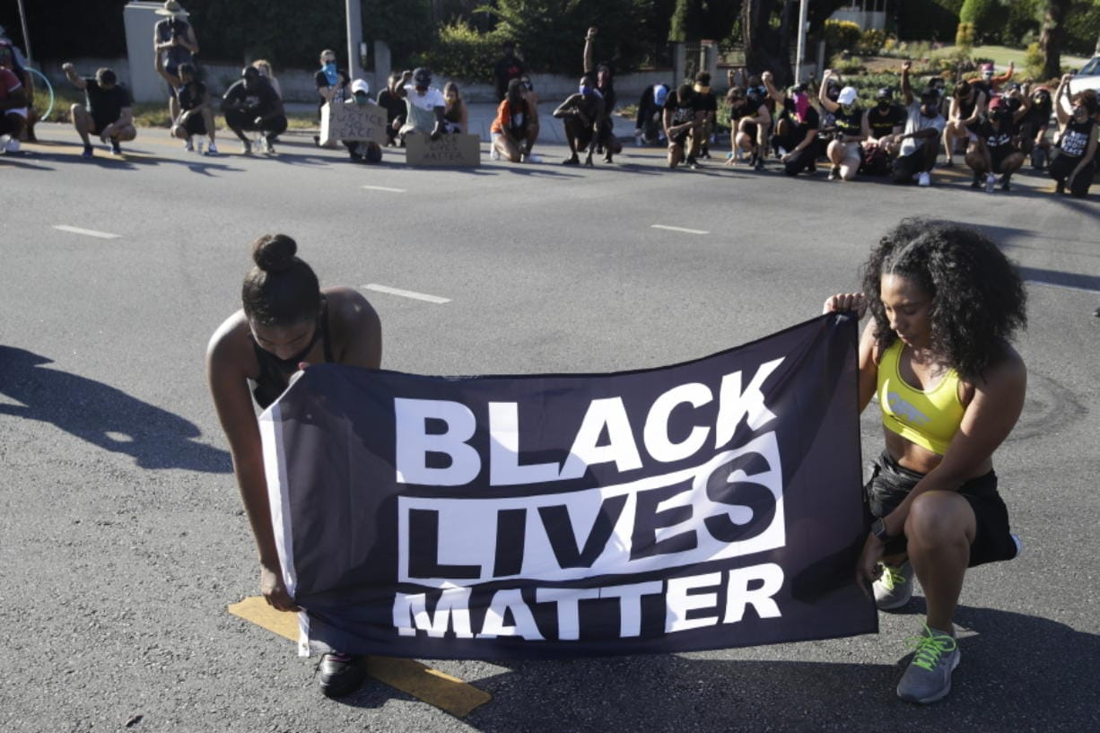 FILE - In this July 11, 2020 file photo, Alycia Pascual-Pena, left, and Marley Ralph kneel while holding a Black Lives Matter banner during a protest in memory of Breonna Taylor, in Los Angeles. Taylor was killed in her apartment by members of the Louisville, Ky., Metro Police Department on March 13. The International Law Enforcement Educators and Trainers Association, a prominent law enforcement training group, is promoting a lengthy research document riddled with falsehoods and conspiracies that urges local police to treat Black Lives Matter activists as terrorists plotting a violent revolution. The document contains misinformation and inflammatory rhetoric that could incite officers against protesters and people of color, critics said.