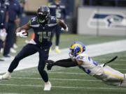 Seattle Seahawks wide receiver DK Metcalf (14) runs after a reception as Los Angeles Rams cornerback Troy Hill (22) attempts the tackle during the first half of an NFL football game, Sunday, Dec. 27, 2020, in Seattle.