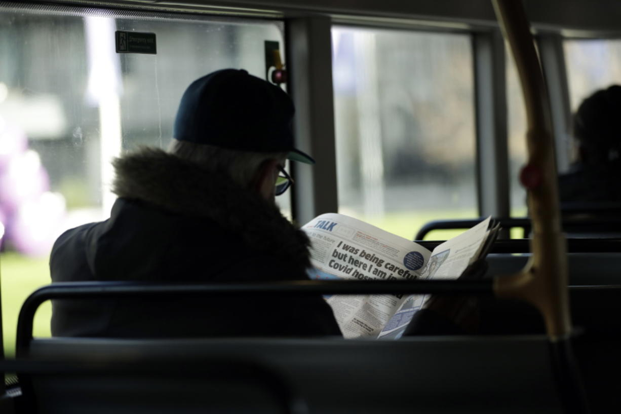 A man reads a newspaper with an article about COVID-19 as he sits on a bus during England's second coronavirus lockdown in London, Tuesday, Dec. 1, 2020. England's second coronavirus lockdown is due to end tomorrow to be replaced by a three-tier system.