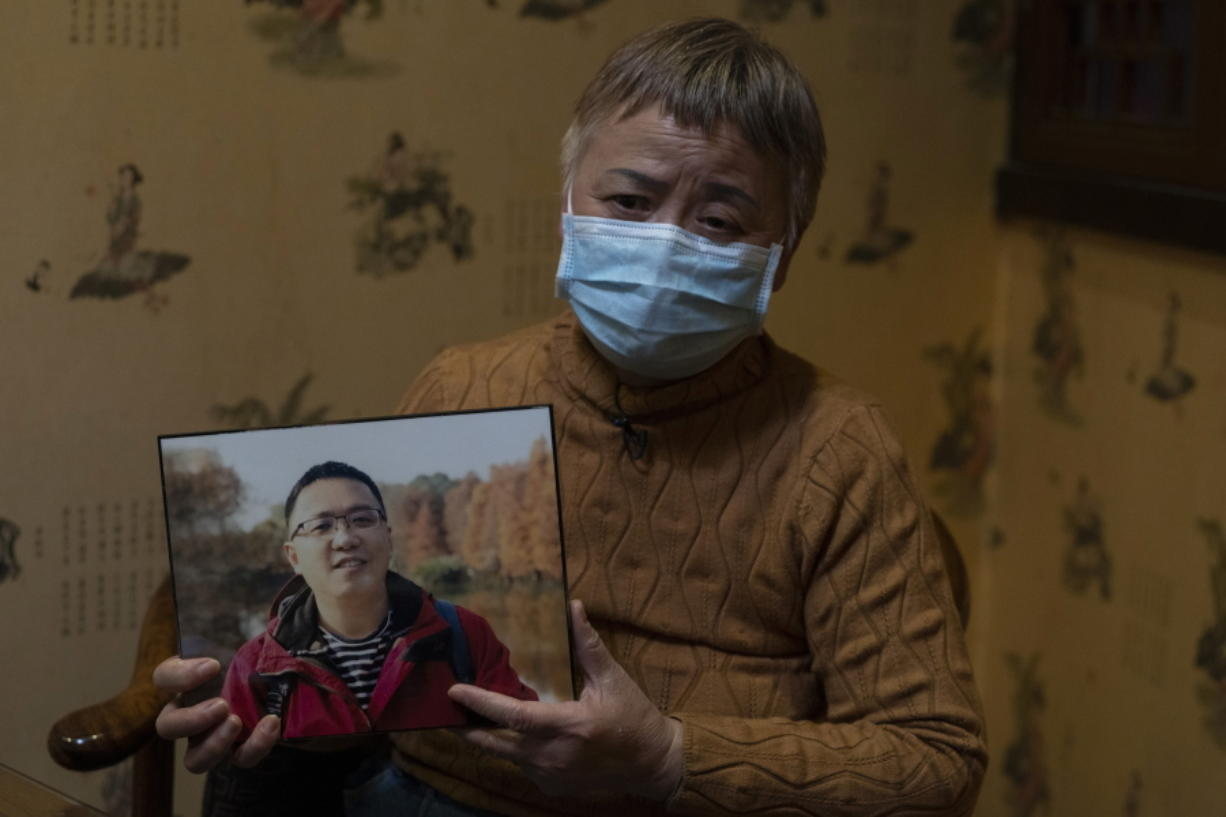 """Zhong Hanneng holds a photo of her son, Peng Yi, and talks about his difficulties in getting tested for COVID-19, eventually dying from the disease, in Wuhan in central China's Hubei province on Saturday, Oct. 17, 2020. """"There were very, very few tests, basically none. ... if you couldn't prove you were positive, you couldn't get admitted to a hospital. ..."""