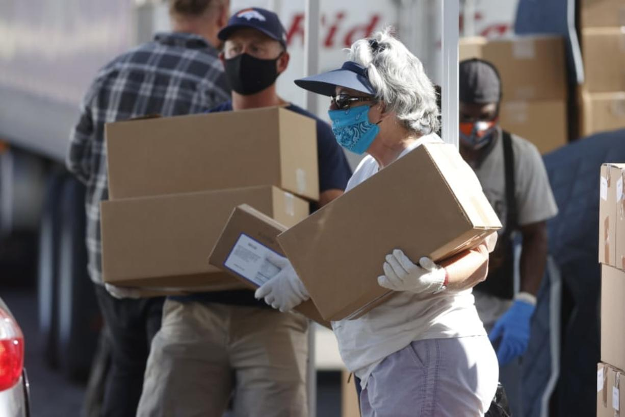 FILE - In this June 26, 2020, file photo, volunteers Juanita MacKenzie, front, and Dave Stutman carry boxes of food to a waiting car at a large mobile pantry set up by the Food Bank of the Rockies in the parking lot of Empower Field at Mile High in west Denver. In an effort to keep Colorado residents fed and employed this winter, Colorado's Legislature is concluding a special session Wednesday, Dec. 2, 2020, by passing bills offering assistance to restaurants and food pantries struggling to keep their doors open during the coronavirus pandemic.