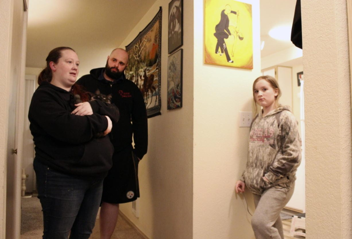 FILE - In this Dec. 11, 2020, file photo, Taylor Wood and her boyfriend, Ryan Bowser, talk to Wood's 10-year-old daughter, Freya Wood, in Corvallis, Ore. The family, which has been living in the apartment for more than two years, has missed three rent payments during the pandemic. As the economic effects of the coronavirus pandemic stretch into 2021, millions of U.S. renters are bracing for the possibility of having to show up in housing court to avoid getting evicted. But unlike their landlords, only a small fraction of them will do so flanked by an attorney.