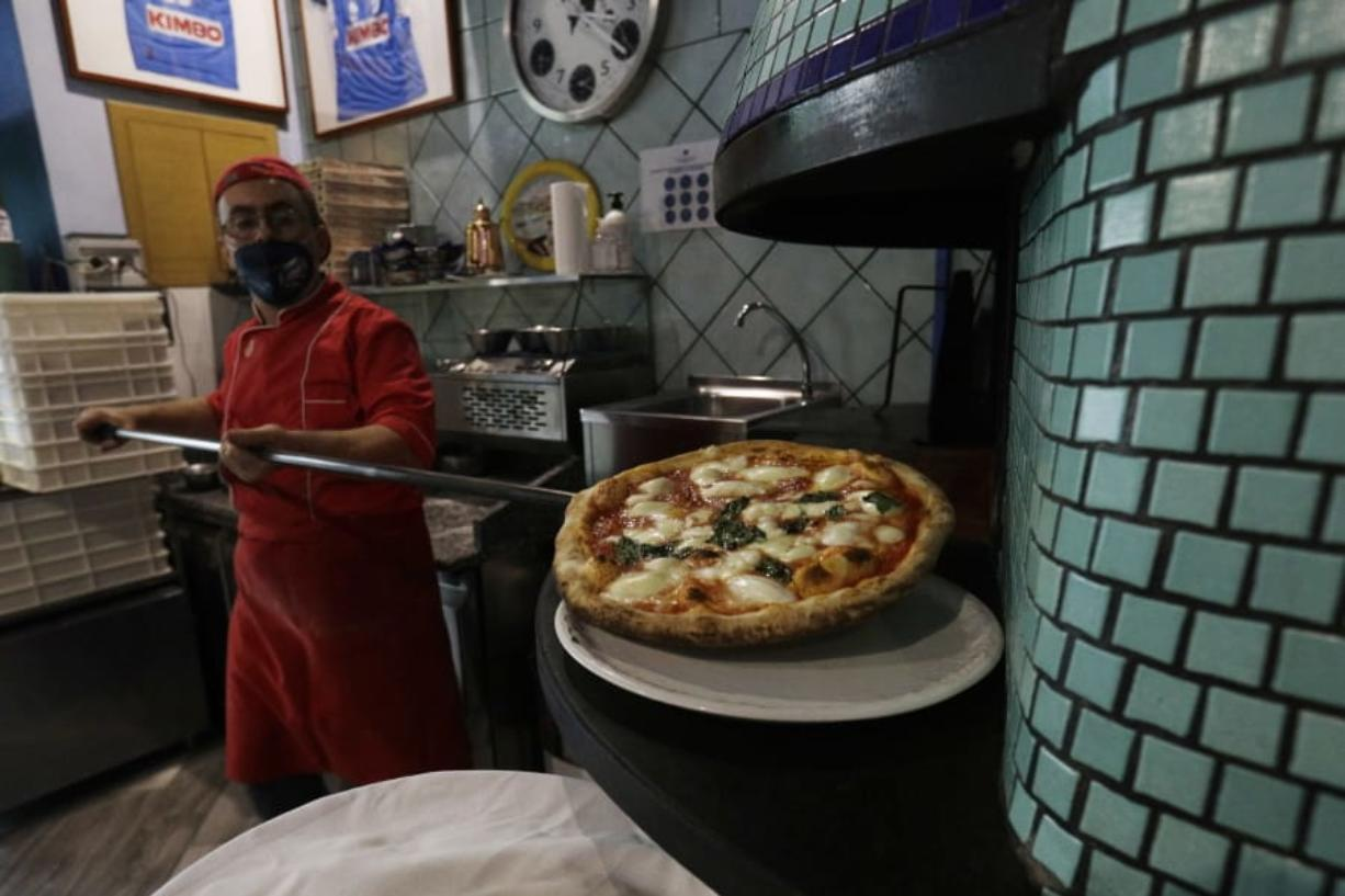 Eugenio Iorio wears a face mask to curb the spread of COVID-19 as he bakes a pizza at a restaurant in Naples, Italy.