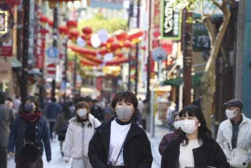 People wearing face masks to protect against the spread of the coronavirus walk through China Town in Yokohama, Kanagawa prefecture, near Tokyo, Tuesday, Dec. 1, 2020.