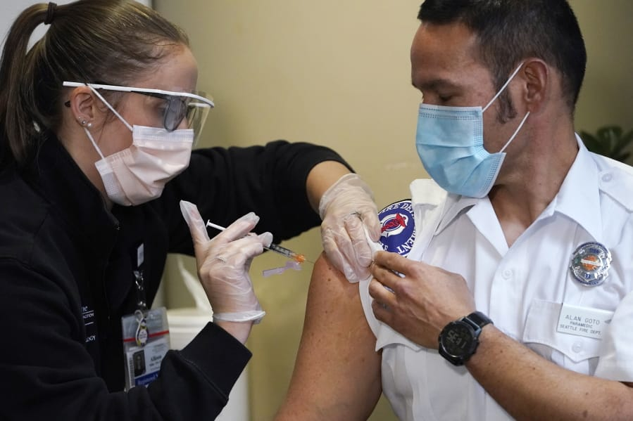 Seattle Fire Dept. paramedic Alan Goto, right, receives one of the first Pfizer-BioNTech COVID-19  vaccinations by registered nurse Allison Miller at UW Medicine, Tuesday, Dec. 15, 2020, in Seattle.