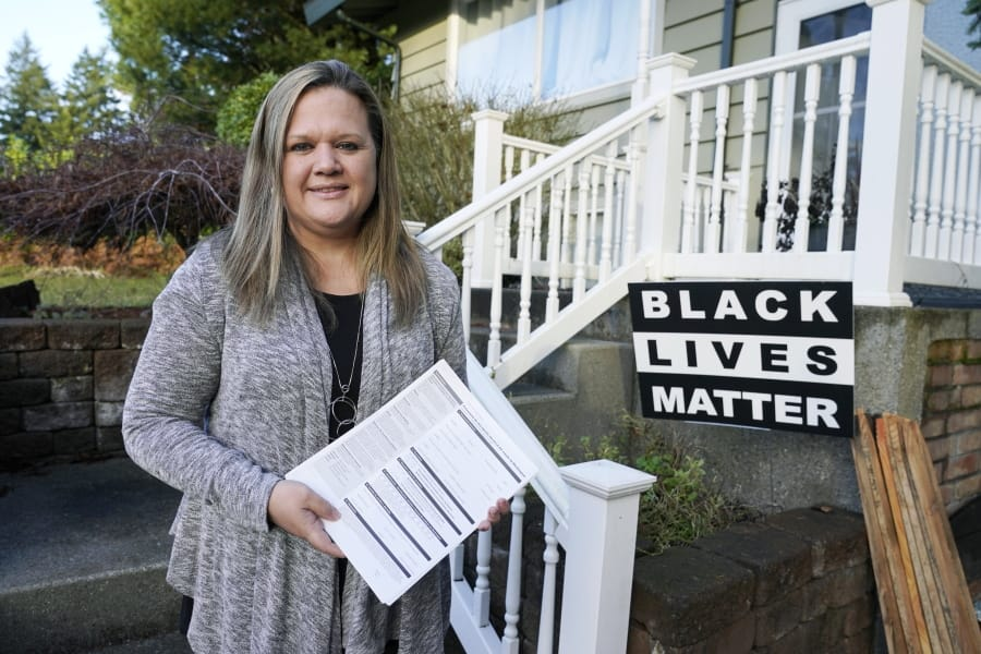 Rep. Tarra Simmons, D-Bremerton, holds blank voter registration forms as she poses for a photo Wednesday, Dec. 9, 2020, at her home in Bremerton, Wash. Simmons, believed to be the first formerly incarcerated person to win election to the Statehouse, is now working to help restore voting rights to people in Washington state who are out on parole or probation after serving prison time. (AP Photo/Ted S.