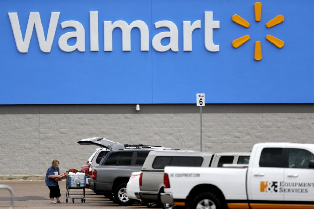 FILE - In this March 31, 2020 file photo, a woman pulls groceries from a cart to her vehicle outside of a Walmart store in Pearl, Miss. Walmart is teaming with the General Motors' Cruise autonomous vehicle unit to test automated package delivery in Arizona.