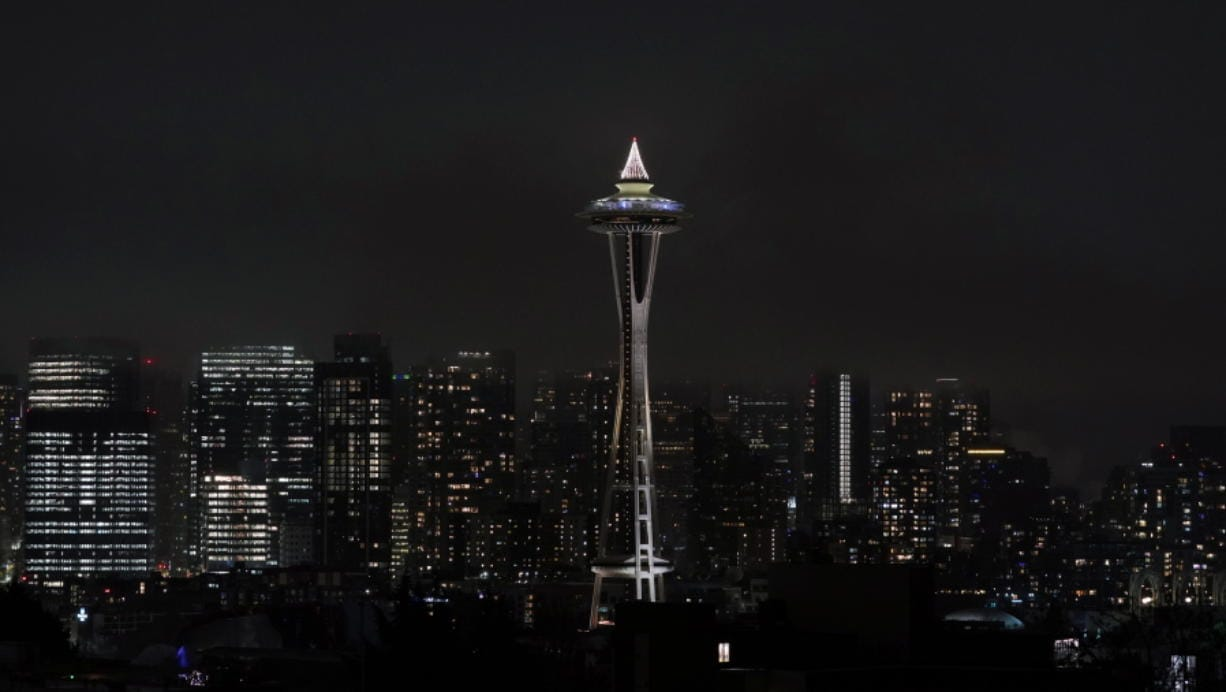 As clouds obscure taller buildings in the background, the Space Needle is shown with holiday lights on top, Monday, Dec. 21, 2020, as viewed from Kerry Park in Seattle. (AP Photo/Ted S.