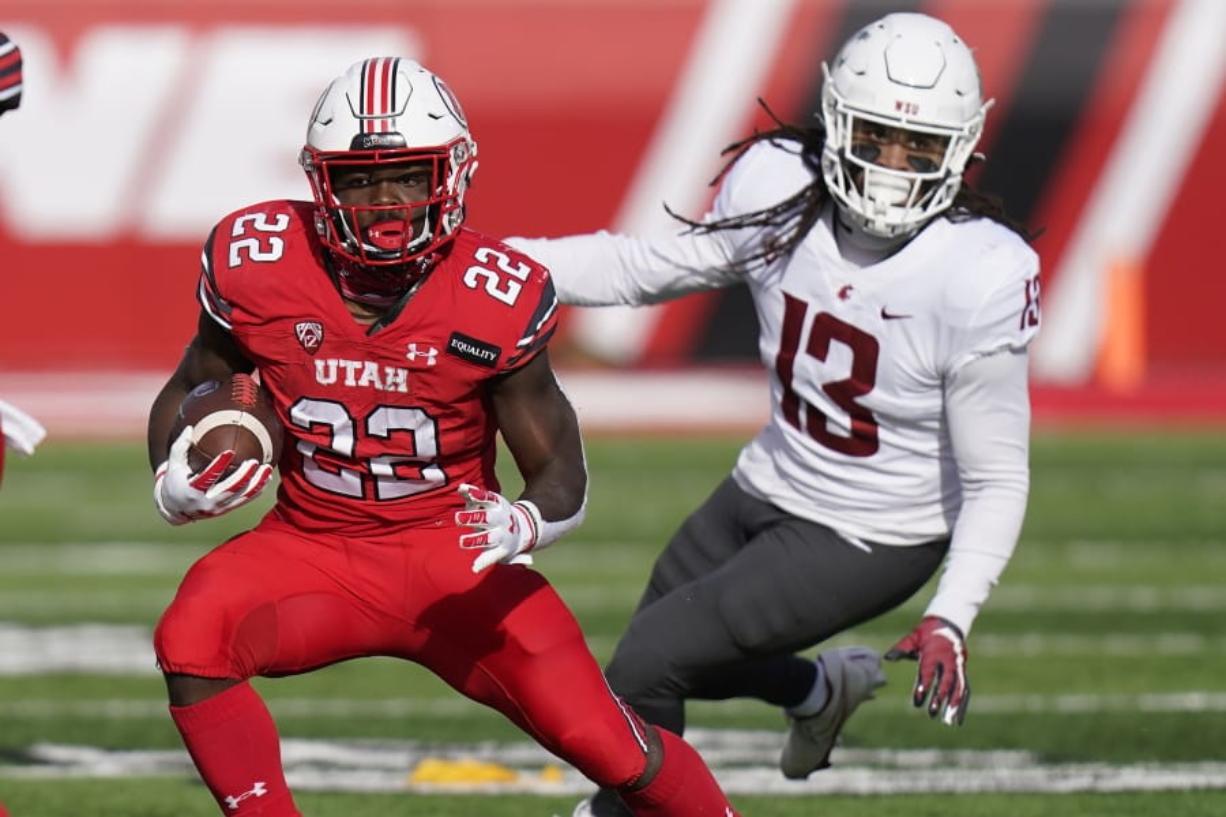 Utah running back Ty Jordan (22) runs from Washington State linebacker Jahad Woods (13) during the first half of an NCAA college football game Saturday, Dec. 19, 2020, in Salt Lake City.