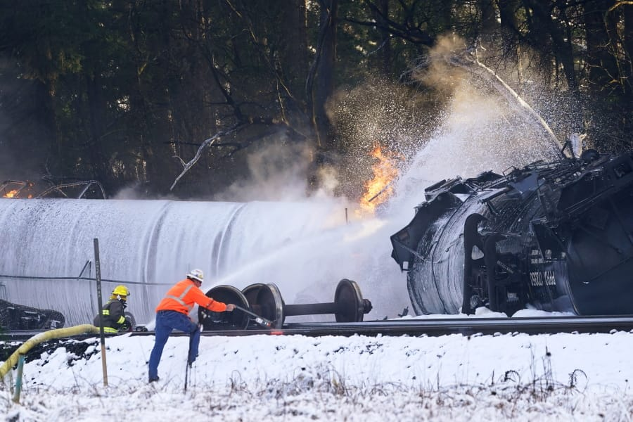 A firefighter sprays foam on a burning, derailed train car Tuesday, Dec. 22, 2020, in Custer, Wash. Officials say seven train cars carrying crude oil derailed and five caught fire north of Seattle and close to the Canadian border. Whatcom County officials said the derailment occurred in the downtown Custer area, where streets were closed and evacuations ordered during a large fire response.
