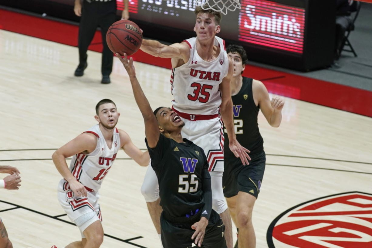 Utah center Branden Carlson (35) defends against Washington guard Quade Green (55) as he goes to the basket during the first half of an NCAA college basketball game Thursday, Dec. 3, 2020, in Salt Lake City.
