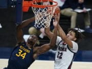 West Virginia's Oscar Tshiebwe (34) and Gonzaga's Anton Watson (22) vie for a rebound during the first half of an NCAA college basketball game Wednesday, Dec. 2, 2020, in Indianapolis.