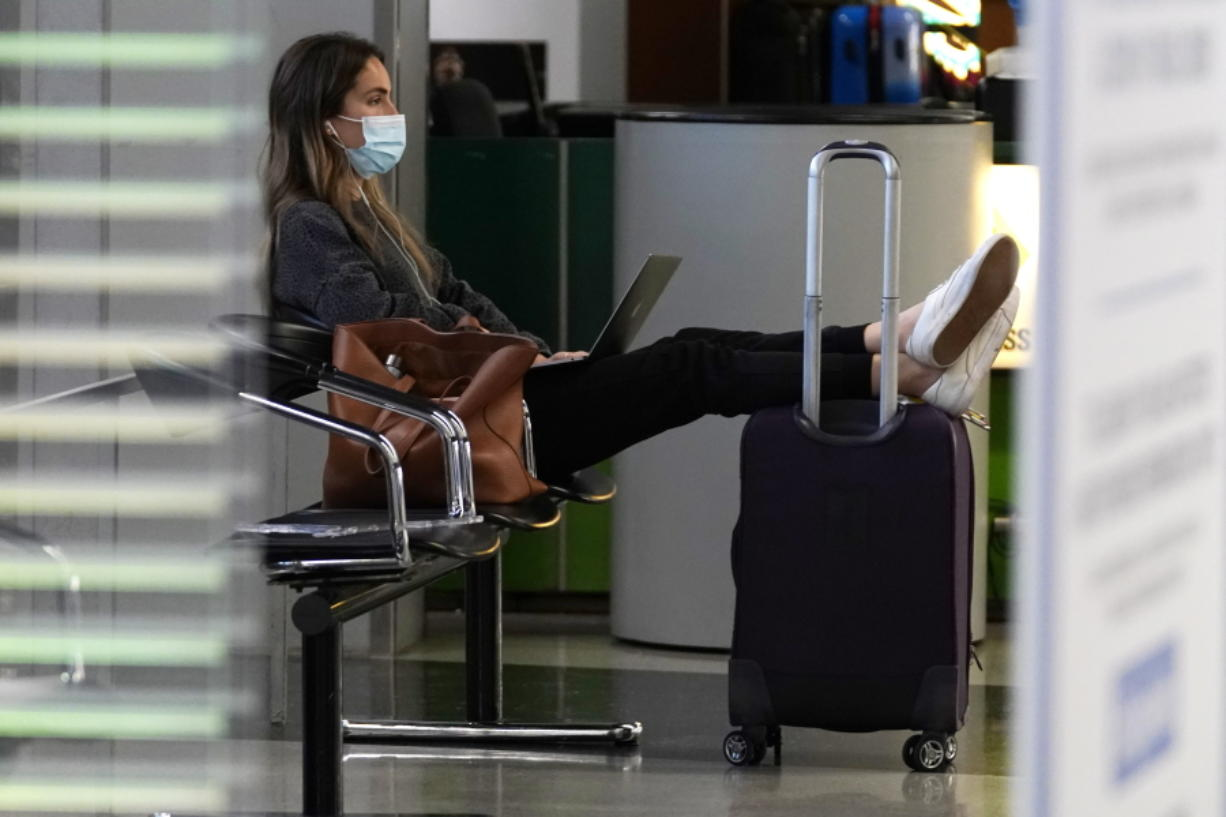 FILE - A traveler wears a mask as she waits for her flight in Terminal 3 at O'Hare International Airport in Chicago, Sunday, Nov. 29, 2020.  The coronavirus pandemic created winners and losers in the business world. Wall Street recovered after March, even though Main Street is still struggling.  As few people traveled, the airline industry needed billions of dollars in aid from the government and is still threatening to lay off workers.(AP Photo/Nam Y.