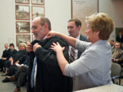 Judge Rich Melnick gets help with his robe from his wife, Lori Melnick, and son Ben Melnick, after he was sworn in as a judge of the Washington State Court of Appeals, Division II at the Clark County Public Service Center on March 26, 2014. Melnick recently retired and was replaced by Judge Bernard Veljacic.
