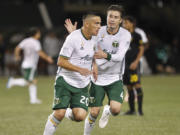 Portland Timbers' David Guzman (20) celebrates his first-half goal against the Columbus Crew during a Major League Soccer match Wednesday, Sept. 19, 2018, in Portland, Ore. At right is Portland's Jorge Villafana.