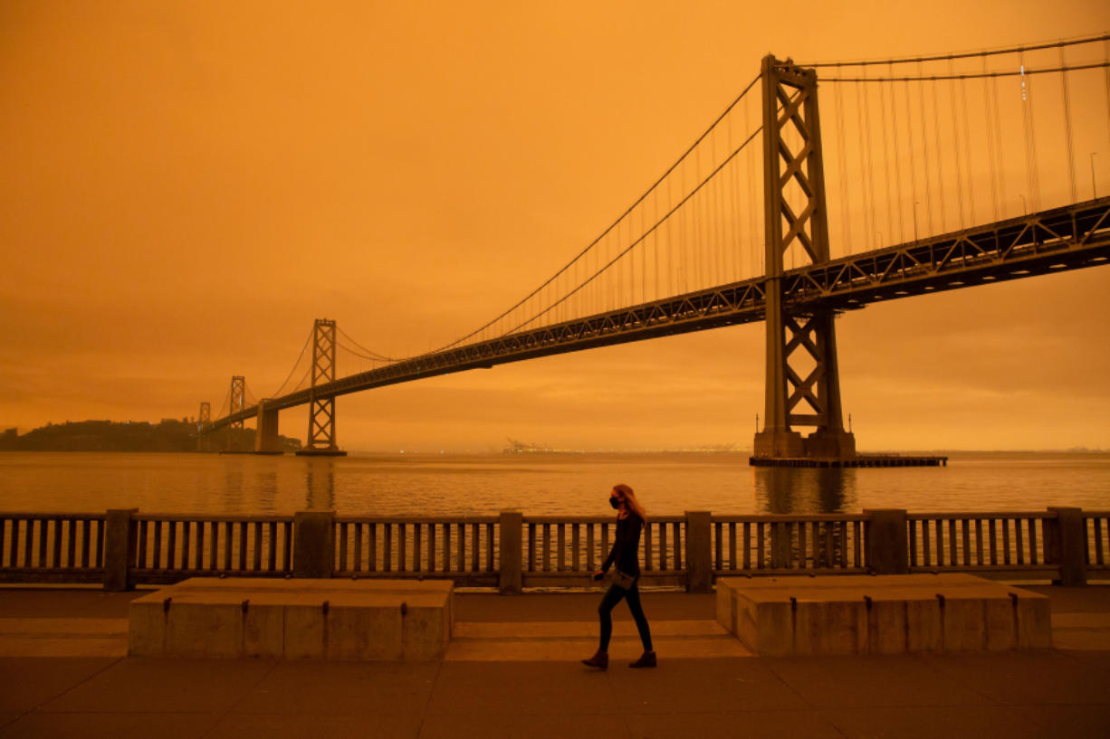 "A woman walks along The Embarcadero under an orange smoke-filled sky in San Francisco, California on September 9, 2020. More than 300,000 acres are burning across the northwestern state including 35 major wildfires, with at least five towns ""substantially destroyed"" and mass evacuations taking place."