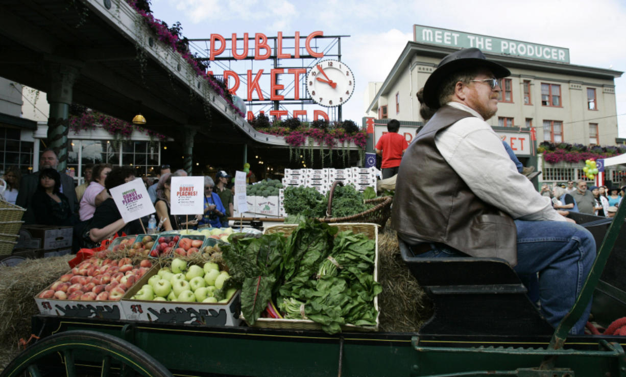 A horse drawn produce wagon driven by Wayne Buckner, of Falls City, sits in 2007 at the Pike Place Market in Seattle.
