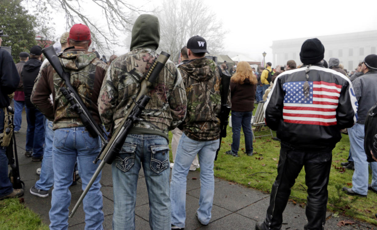 """Demonstrators with rifles slung across their backs attend a rally by gun-rights advocates to protest a new expanded gun background check law in Washington state Saturday, Dec. 13, 2014, in Olympia, Wash. Saturday's protest was called the """"I Will Not Comply"""" rally, and those attending said they will openly exchange firearms in opposition to the state's new voter-approved universal background check law, Initiative 594. The law, which took effect on Dec. 4, requires background checks on all sales and transfers, including private transactions and many loans and gifts."""