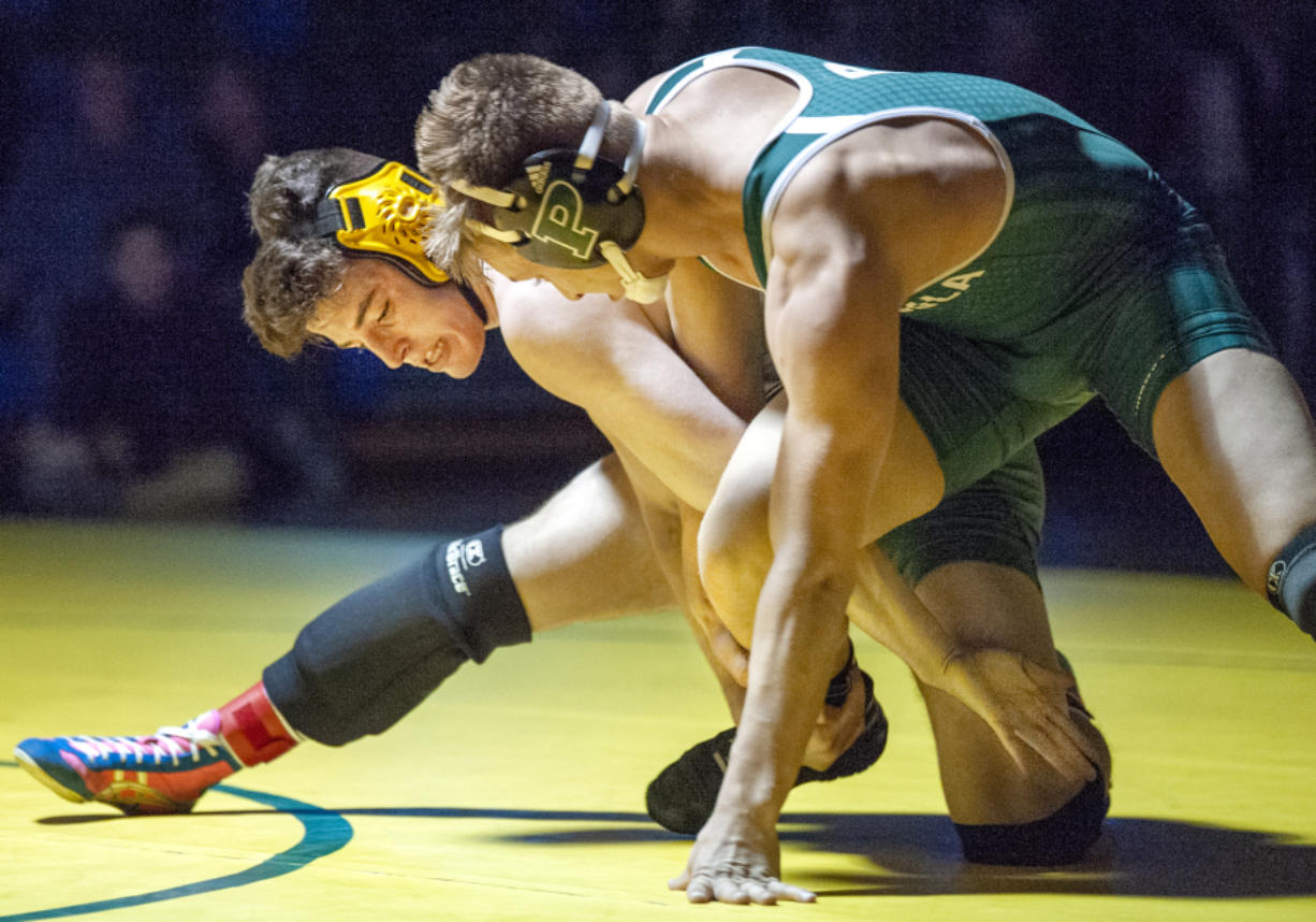 Heritage's Alex Newberry, left, wrestles at the Pacific Coast Championships in Dec. 2019. An amendment proposed by Heritage wrestling coach Erik Gonzalez would make such two-day tournaments count as one of a wrestling team's 16 allowed team events.