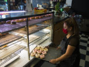 Jessica Sanchez, co-owner of Tonallis Doughnuts & Cream, looks over a selection of fresh doughnuts. Business has been slow for Tonallis during the pandemic, but Sanchez said she has faith that it will pick up.