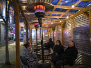 Heaters at the outdoor dining area of the Main Event in downtown Vancouver add warmth for customers Alyson Hilken, from left, Krissy Sadewasser and John Laughlin as they enjoy a happy hour drink.  At top, a sign informs customers of alternative dining options at Main Event.